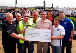 Gary Wilson of the British Heart Foundation NI is presented with a £915 cheque from members of the Ford Fair committee at the Ford Fair in Portrush in 2009